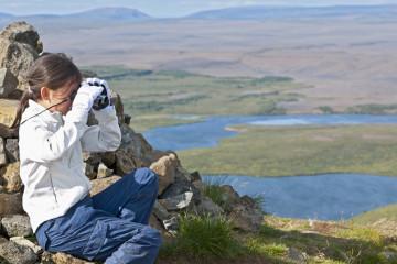 Girl examining landscape with binoculars