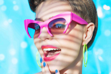 Colorful summer portrait of young attractive woman wearing sunglasses under a palm tree by the swimming pool
