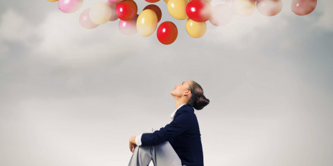 Young pretty businesswoman sitting on top of building with colorful balloons flying above