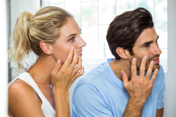 Close-up of man and woman in bathroom applying moisturizer on their face