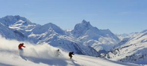 skifahrer_bei_abfahrt_vor_bergpanorama_ski_arlberg