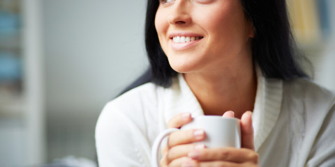 Portrait of happy brunette with mug in hands