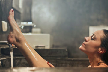 Frau entspannt und pflegt sich in Badewanne