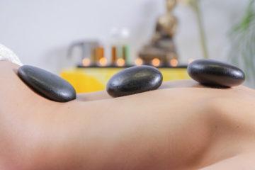 Frau liegt auf Bauch bei Hot Stone Massage