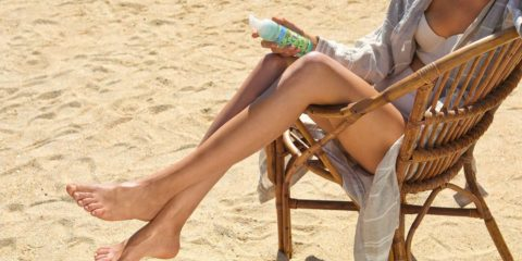 Sonnengebräunte beine einer Frau mit Pflegelotion auf Stuhl am Strand