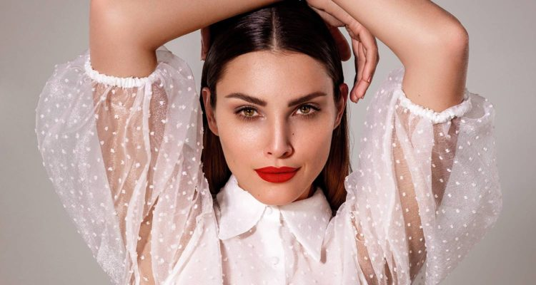 Frau mit starkem Make-up verschränkt Arme über dem Kopf