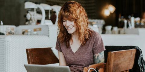 Junge brünette Frau mit Tattoos sitzt im Café am Laptop beim Online-Shopping