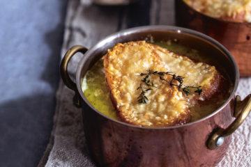 Zwiebelsuppe mit Käsekruste in Messingtöpfchen