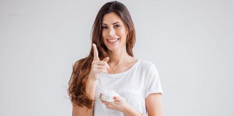 Junge brünette Frau mit Cremetiegel in der Hand und etwas Creme am Finger
