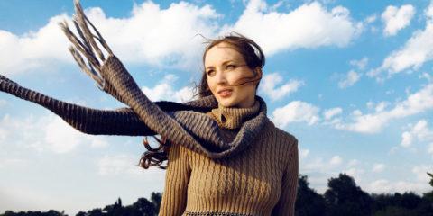 Frau mit Schal und Pullover im Herbst vor blauem Himmel
