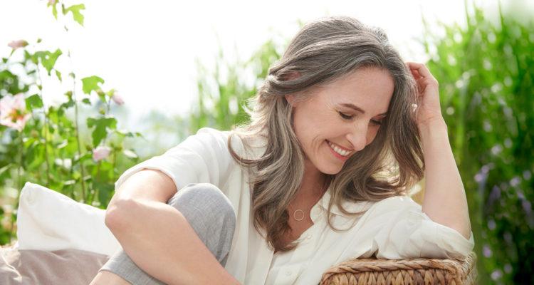 Ältere Frau sitzt auf Gartenbank im grünen